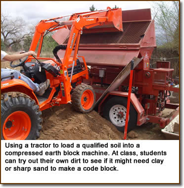 Using a tractor to load a qualified soil into a compressed earth block machine. At class, students can try out their own dirt to see if it might need clay or sharp sand to make a code block.