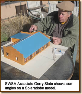 SWSA associate Gerry Slate checks sun angles on a Solaradobe model.