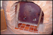 A view of the Grubka's firebox steel door with typical wood fuel of small diameter.