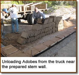 Unloading Adobes from the truck near the prepared stem wall.